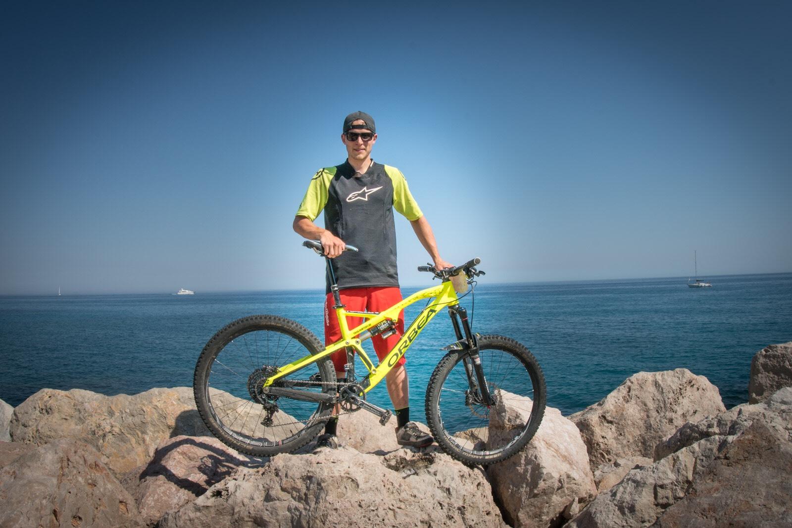Job Bokmans staat met zijn Orbep op een stapel grote stenen voor de zee