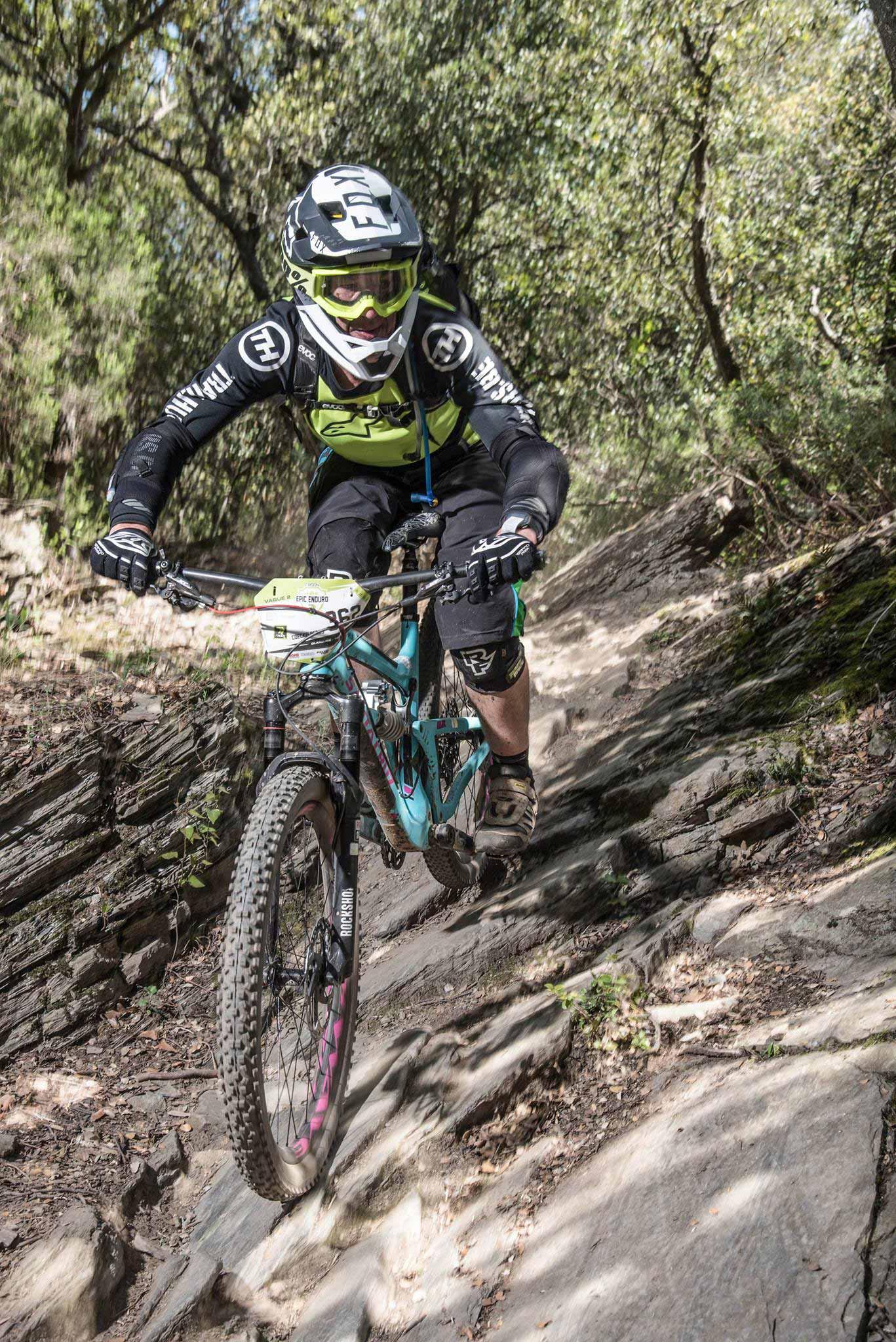 Bart rijdt over een trail vol met rotsen. Hij heeft zijn fullface helm op en kijkt strak de bocht in,