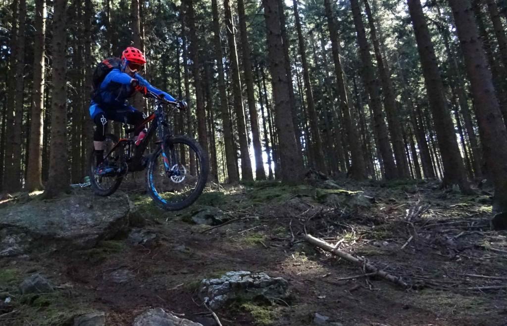 Mikey springt met zijn MTB over een rotsblok heen. Het is donker in het Belgische bos