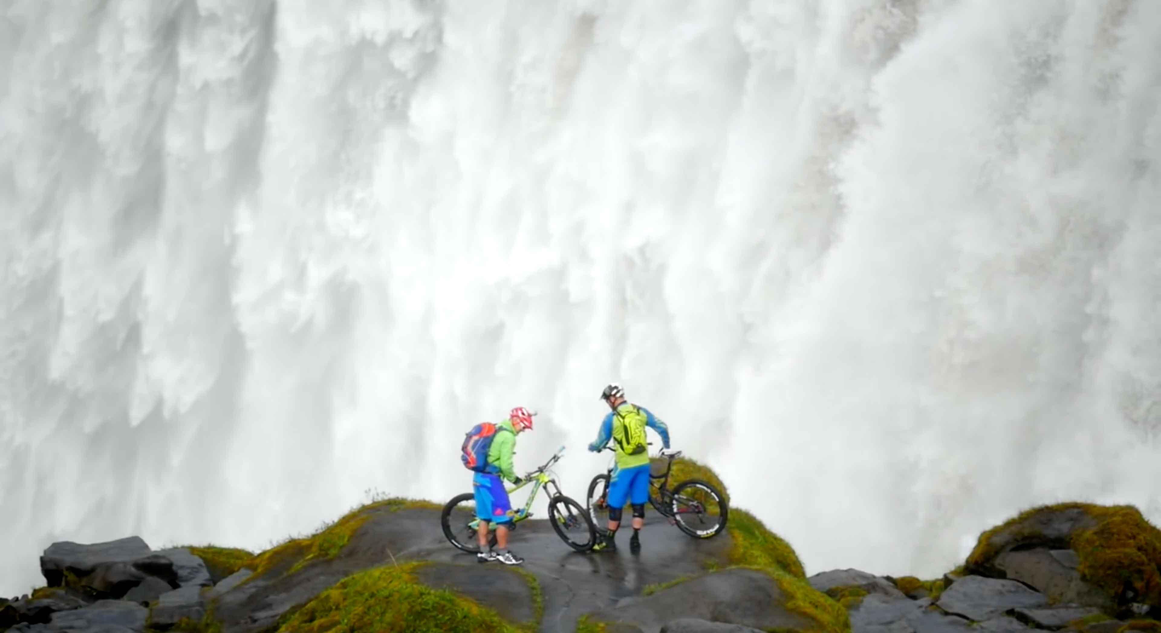 Grote waterval met 2 mountainbikers ervoor