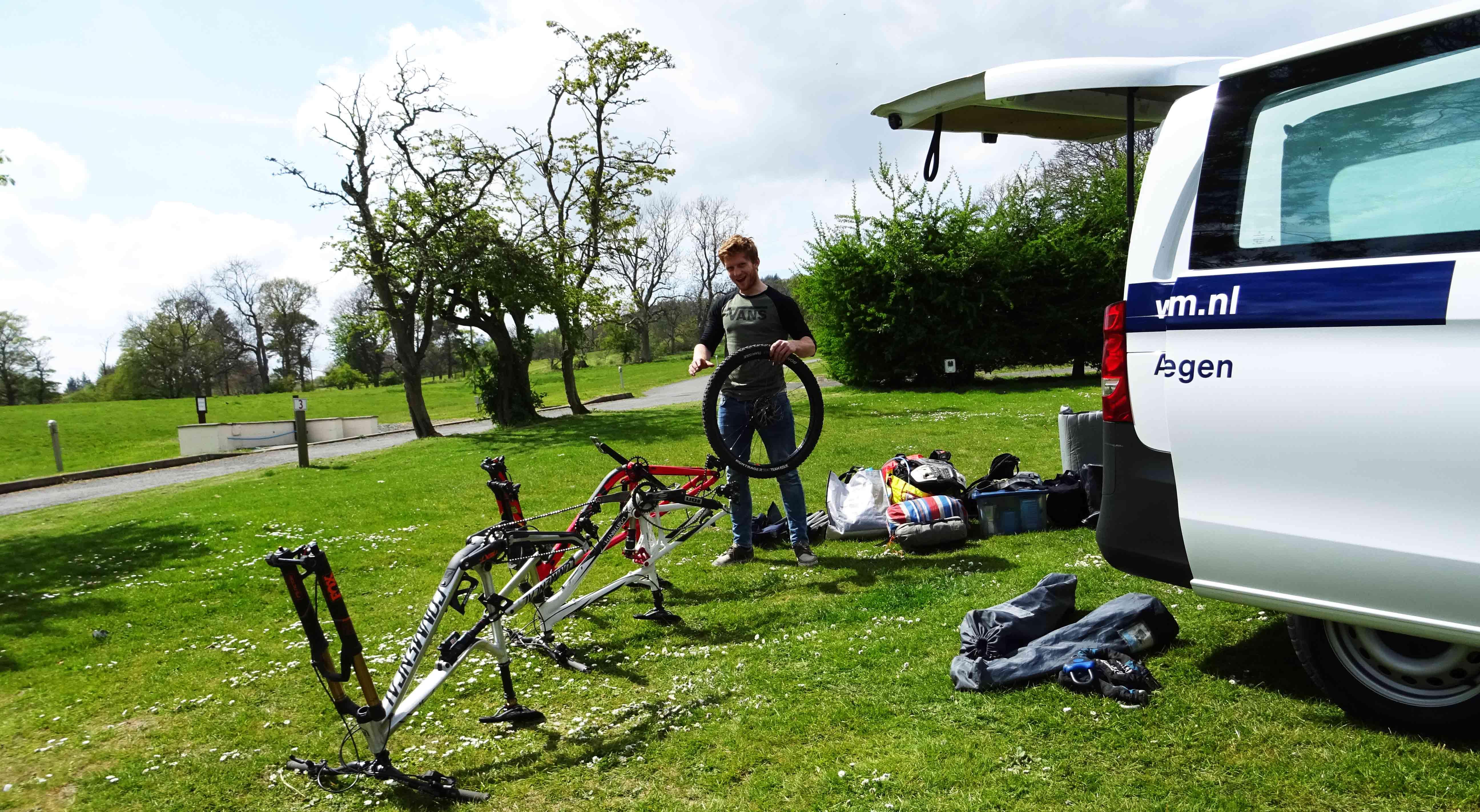 Hielke sleutelt de bikes in elkaar op de camping
