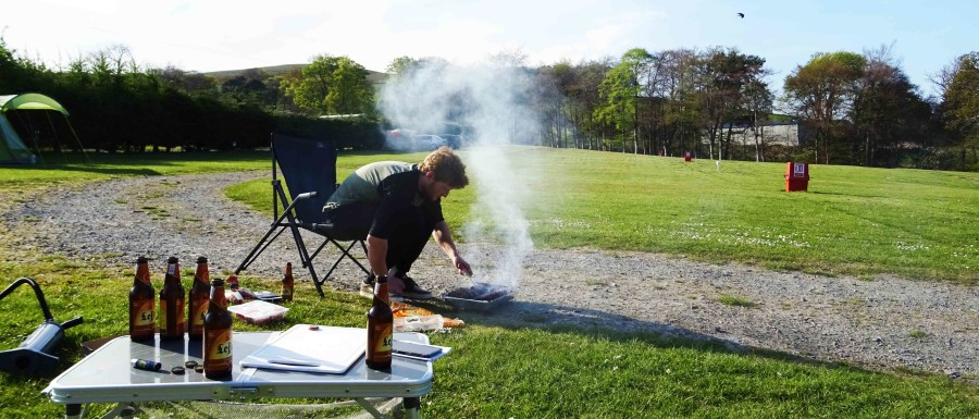 Hielke draait het vlees op de wegwerp BBQ op de camping.