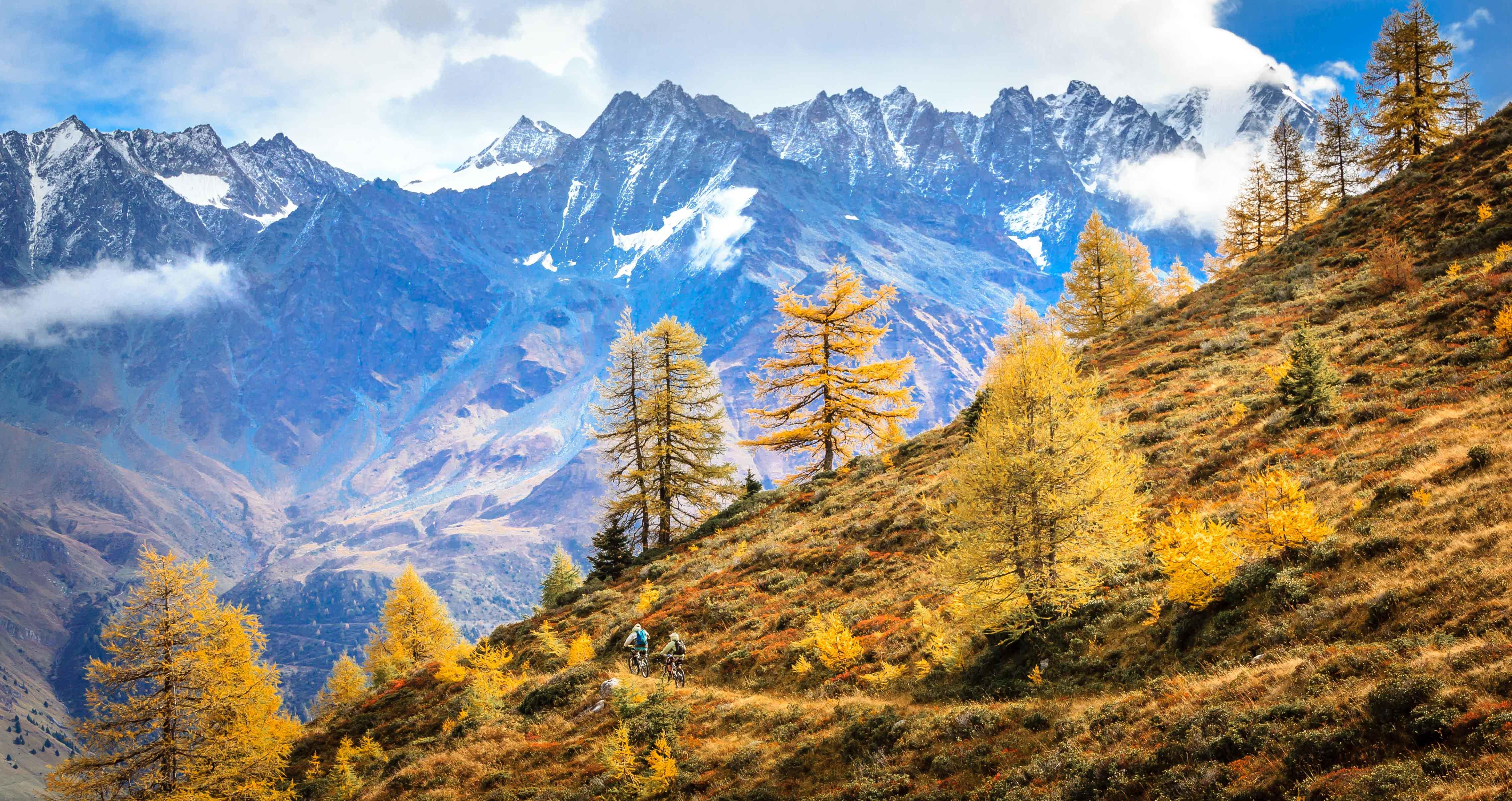 Oktober in Wallis, 2 mountainbikers die fietsen langs een prachtige goudgele bergwand in Zwitserland