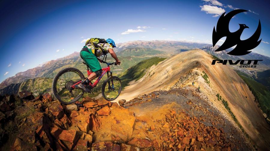 Een mountainbike rijdt over een ridgline. De rotsen zijn goud gelig van kleur met een strak blauwe lucht