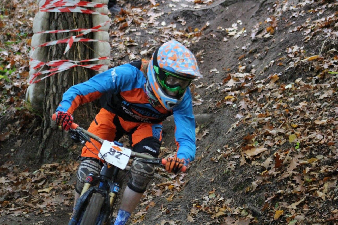 Rob rijdt met zijn fullface helm hard door een bocht tijdens de downhill wedstrijd