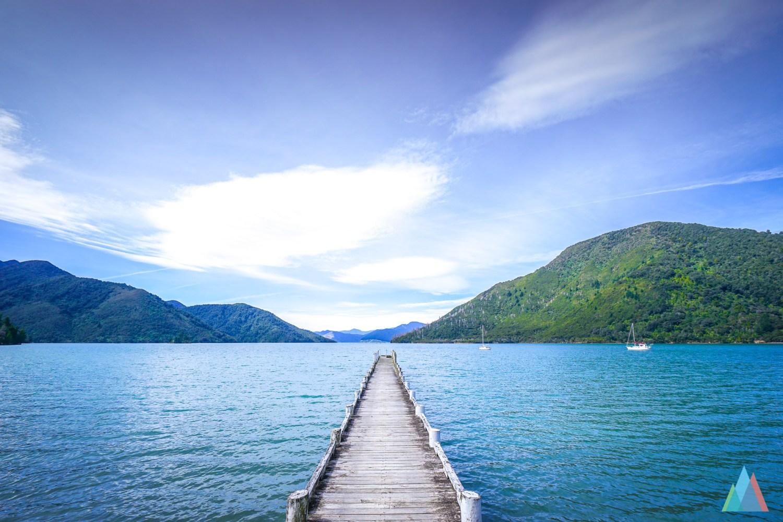 Een kaarsrechte houten pier op een meer in Nieuw-Zeeland