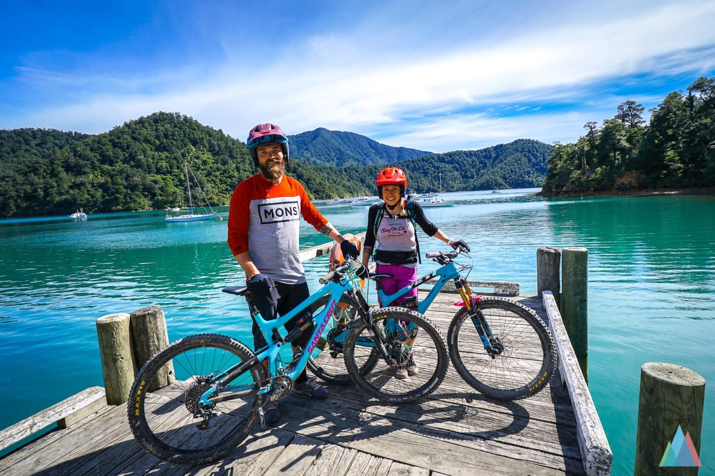 Ben en zijn vriendin staan op een houten pier op een meertje met hun bikes. Ze kijken tevreden van een dag trails rijden!