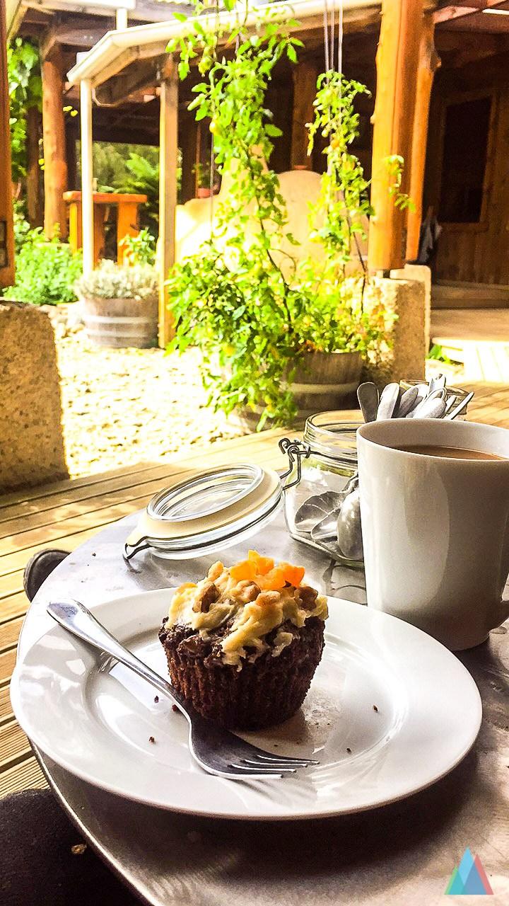 een gebakje ligt op een schoteltje naast een bak verse koffie
