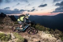 Bart rijdt over een trail bij zonsopgang. De goede gloed stroomt langzaam de bergen in.