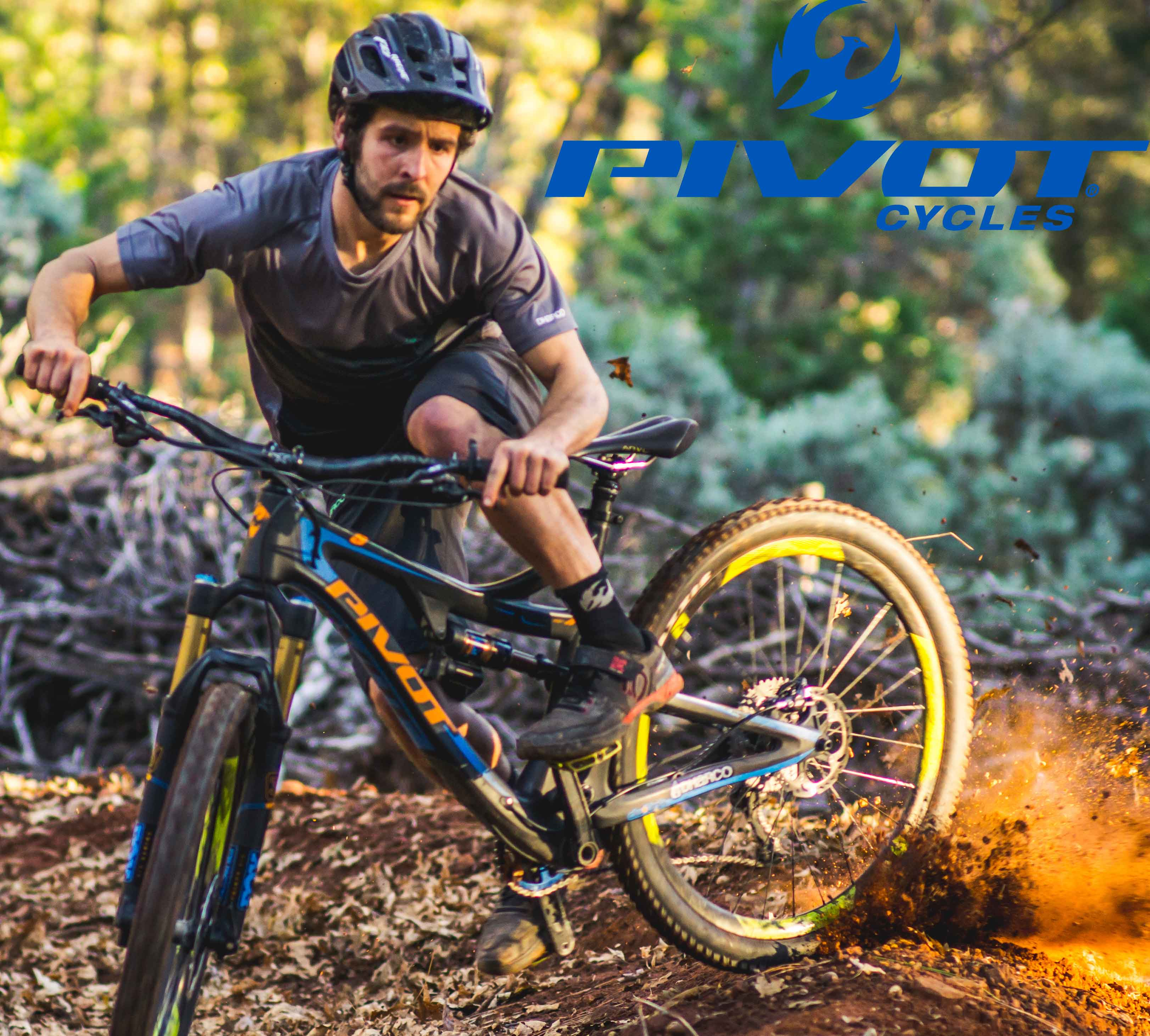 Mountainbiker drift door een bocht. Het goud gele zand spat hoog op.