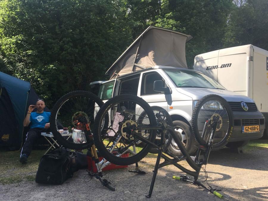 Volkswagen T5 camper met het hefdak omhoog. 2 mountainbikes staan op de kop voor het kleine kamp