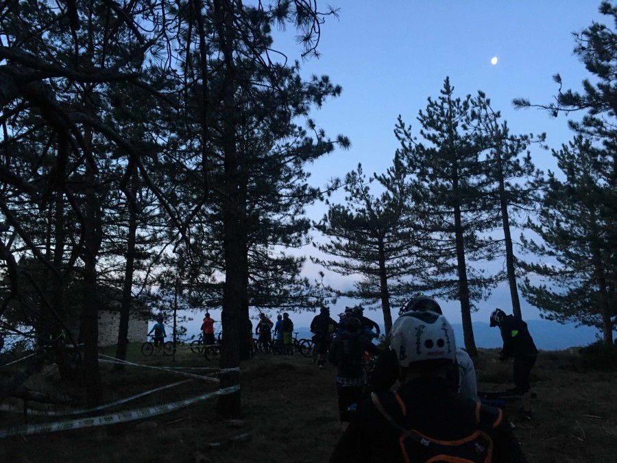 Veel mountainbikers staan te wachten op een berg. De maan is zichtbaar en de zon komt rustig op. Het is helder weer maar erg koud