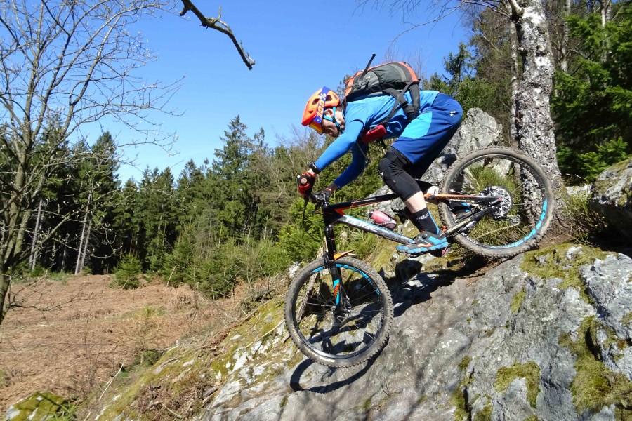 Een mountainbiker rijdt een steile rotswand af in Remouchamps. Het weer is strak blauw!