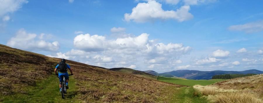 Rik klimt omhoog door een weids landschap in Schotland