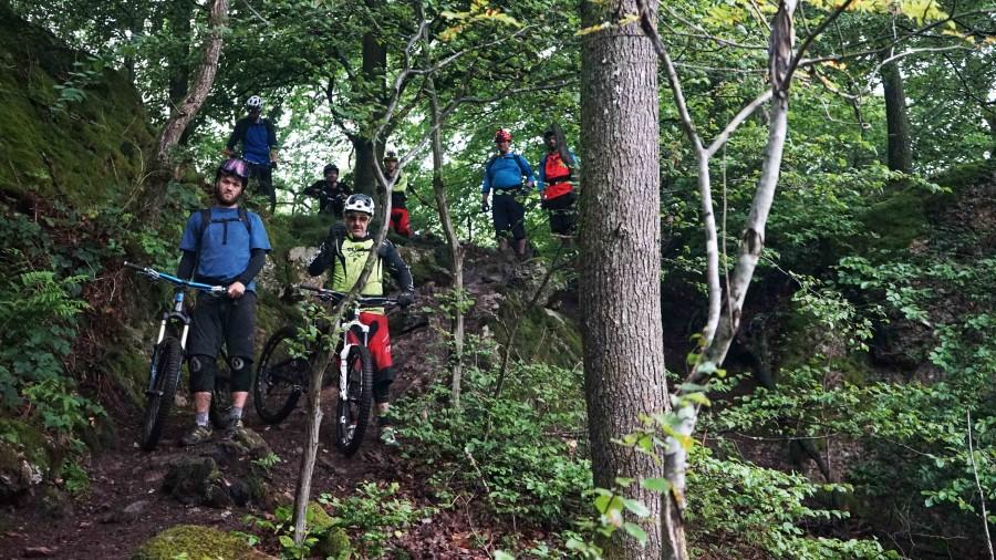 7 mountainbikers checken de afdaling voordat ze beginnen