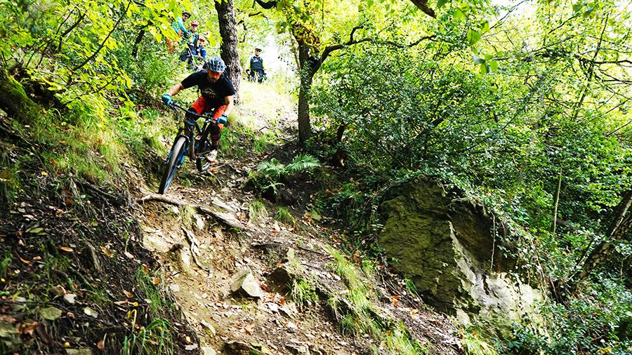 Nick rijdt over een wortel op een steil stuk trail