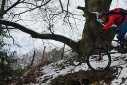 Mountainbiker rijdt een drop af in een met sneeuw bedekte afdaling