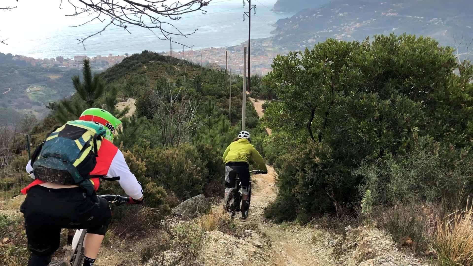 3 mountainbikers rijden een trail in met uitzicht op de zee en finale ligure