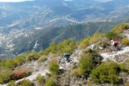 2 bikers rijden over een berg rug met finale ligure op de achtergrond