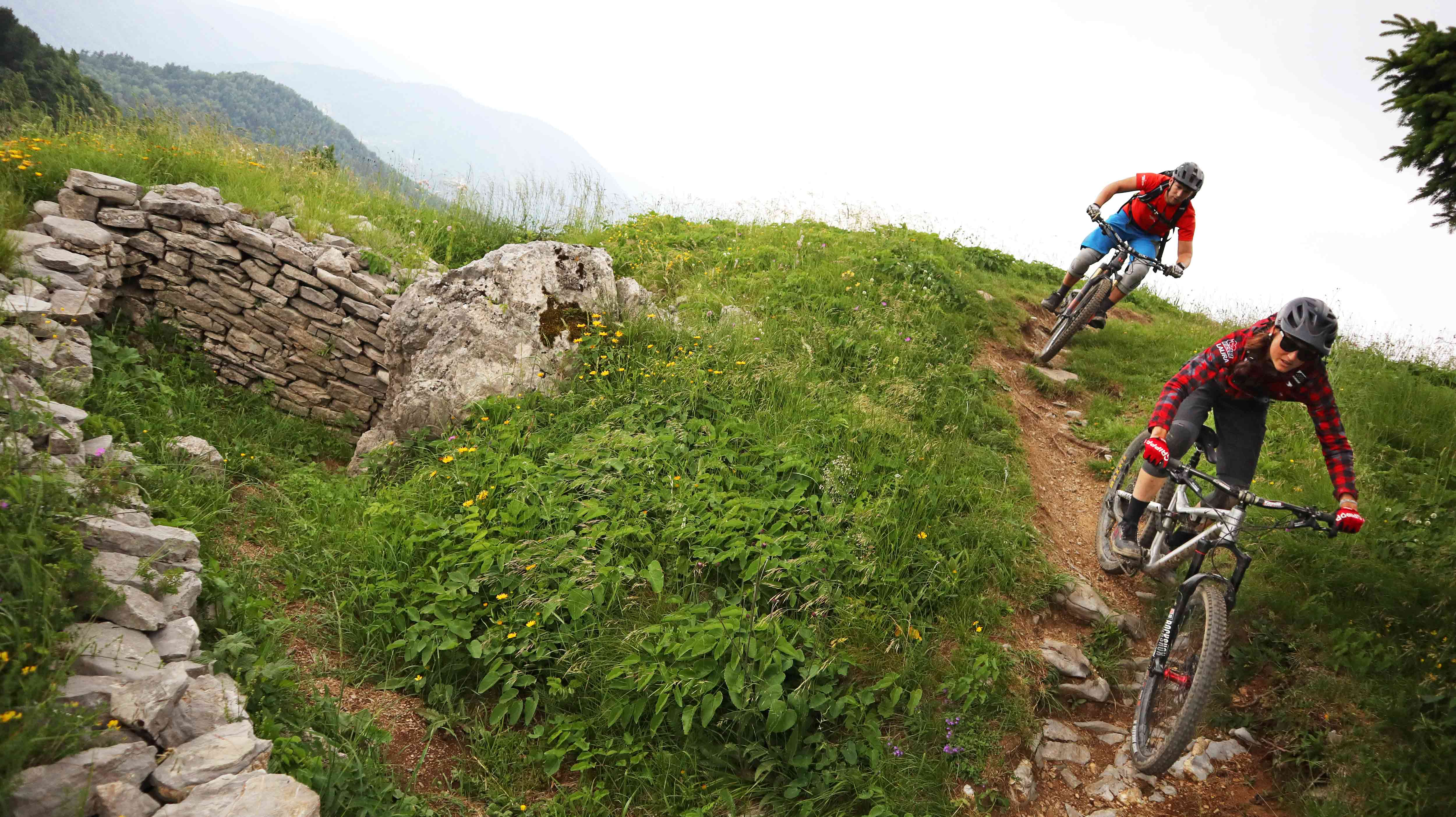 A trail with 2 riders near an old wall in slovenia