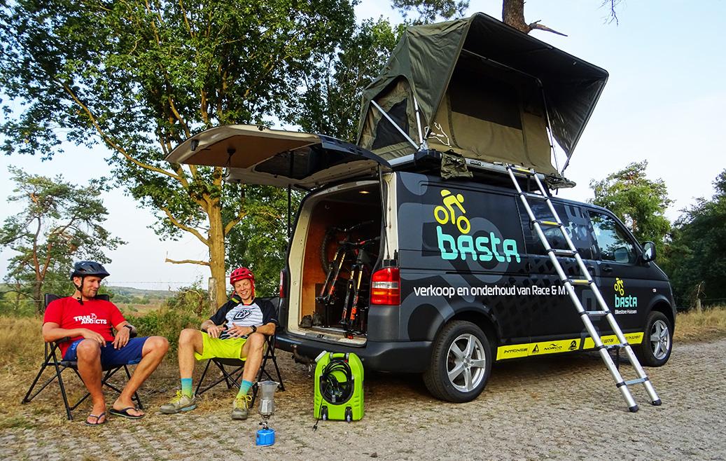 2 mountainbikers zitten voor de bus met daktent te wachten tot de koffie klaar is